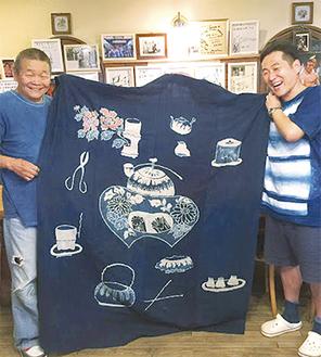 撮影に使った筒描を持つ堀内社長(左)と杉戸さん