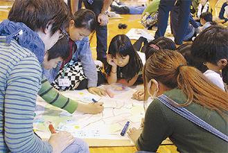 地図を見ながら議論する子どもら