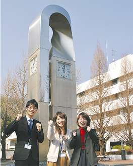 シンボルの時計台の前で喜びを表す卒業生の職員