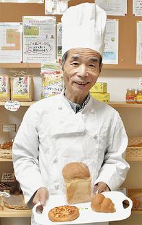 笑顔で自慢のパンを紹介する村上さん