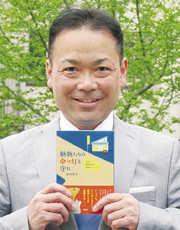 本を手に喜ぶ細田さん