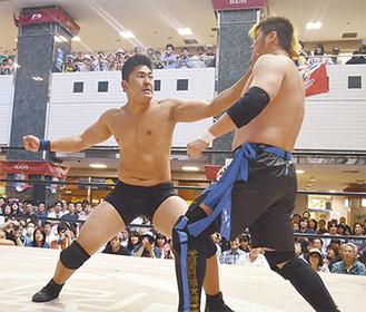 観客の前で熱戦を繰り広げるレスラー