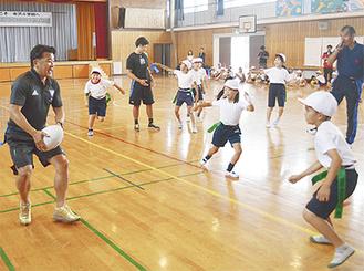児童とタグラグビーをプレーする吉田さん(左)