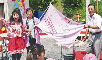 旗を寄贈する篠崎さん(左)