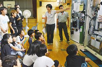 自動販売機の内部を見る児童