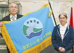 実行委員会から贈られた校旗を持つ桐山校長(左)と上村実行委員長