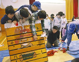 「横浜防災ライセンス・磯子」のメンバーにレスキュージャッキの使用法を学ぶ児童