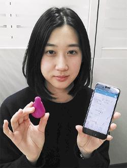 ビーコン(左)とアプリをインストールしたスマホを持つ京急電鉄の田名部さん