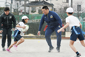 児童にタグラグビーを指導する相馬さん