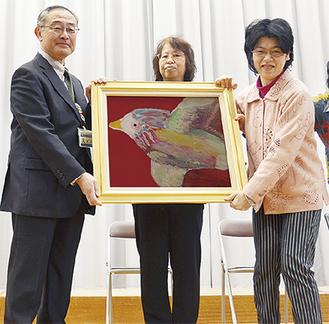 塚田さん(右)から斎藤校長に「光」が贈られた。中央は母親のとみ子さん