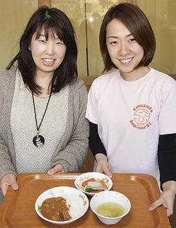 給食を持つ芳尾園長(左)と管理栄養士の鈴木葉月さん