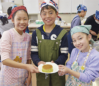 米粉で作ったケーキを持つ児童
