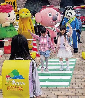 手を挙げ仮設横断歩道を渡る新1年生(提供・金沢交通安全協会)