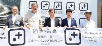 テープを持つ隈氏(左から2人目)、佐藤氏(右から2人目)ら