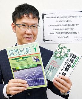 小竹代表著書の「葬儀・法要・相続 備えと手続きがわかる本」(右)と月刊コラムを担当している「電気計算」。写真後ろには生島ヒロシさんからのメッセージも