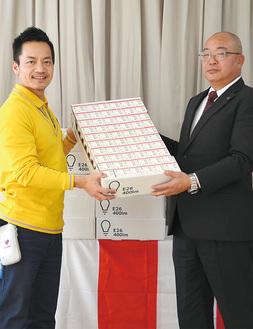 電球を寄贈する南マネージャー(左)と受け取る森野会長