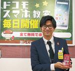 らくらくスマートフォンを持つ神坂副店長