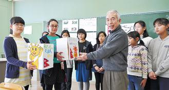 平綿さん(中央)に文房具を渡す児童