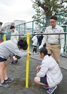 鉄棒にペンキを塗る児童
