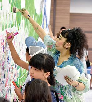 子どもたちと絵を描く蟹江さん(右)