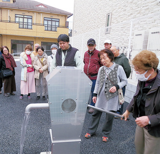 手動式の防災井戸を試用する地域住民