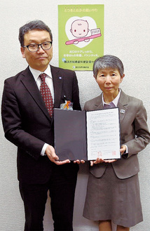 協定書に押印した市担当者と市歯科医師会杉山会長(右)