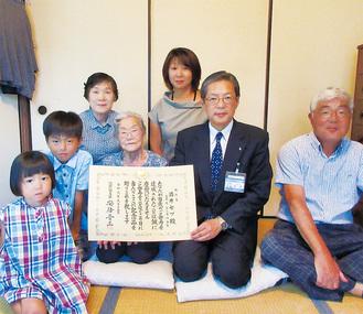 猪俣区長から祝状を手渡された酒井さん(中央)