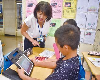 タブレットの操作法を教えるICT支援員