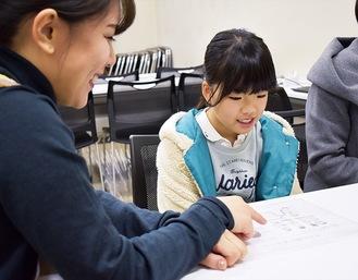 学童期調査の説明をうける帯谷朋花さん(右)