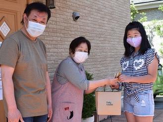 作ったマスクを手渡す高須さん(右)