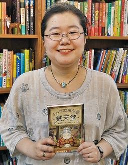 著書を手に笑顔を見せる廣嶋さん