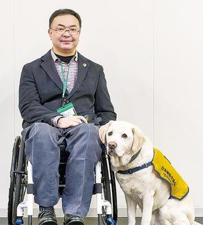 協力を呼びかける安杖さんと介助犬(同協会提供)