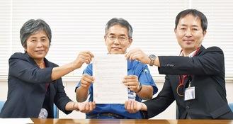 調印書を手にする平野局長、松嵜所長、東局長(右から)