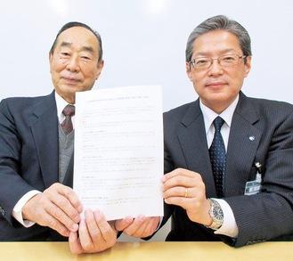 協定書を持つ小川会長(左)と猪俣区長