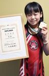 優勝した大会のメダルと賞状を持つ田中愛莉さん