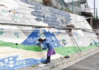 塀一面に絵を制作する保護者たち