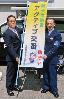 のぼり旗を持つ及川会長(左)と熊田署長