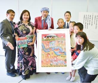 寄贈された絵を持つ児童ら