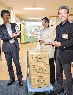 寄付品の水を手にする若色校長、関さん、安藤代表(右から)