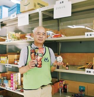 空きが目立つ棚の前に立つ藤田事務局長