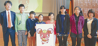 新しく生まれ変わったウメニーを手にする児童らと、尽力した安藤代表取締役(左端)