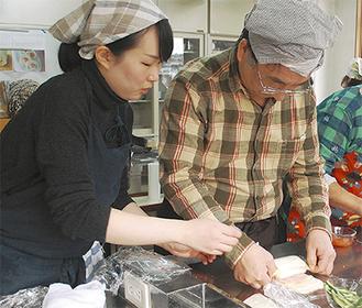 佐藤さん(左)の指導を受けながらサンドイッチを巻き上げる参加者
