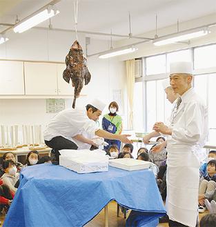 アンコウの吊るし切りについて説明する松崎料理長