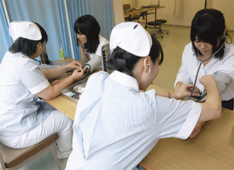 血圧測定を受ける高校生