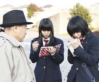 初挑戦にも臆せず、217系統の利用者に取材する青木さん(右)と松浦さん(中央)