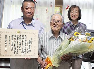 花束を手にする笠原さん(中央)