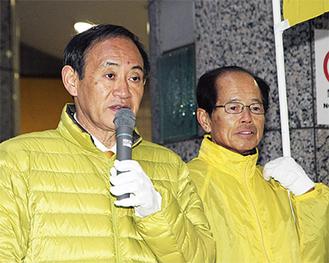 当選翌日の17日朝、上大岡駅前で報告を行った菅氏(左)