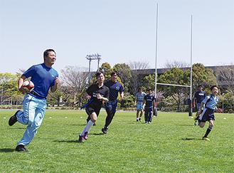 青空の下、学生と汗を流す子どもたち=4月4日、関東学大釜利谷グラウンド