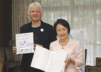 ヤン氏(左)が林市長に楽譜を手渡した