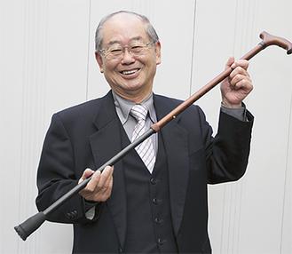 ラクーンシリーズを付けた杖を持つ飯田社長